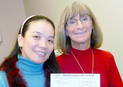 Qing holding her GED certificate with her tutor.
